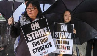 Faith Park, 13, holds a sign in support her mother Sarah Lee-Park during a teacher strike outside John Marshall High School, Monday, Jan. 14, 2019, in Los Angeles.Tens of thousands of Los Angeles teachers are striking after contentious contract negotiations failed in the nation's second-largest school district.(AP Photo/Ringo H.W. Chiu)