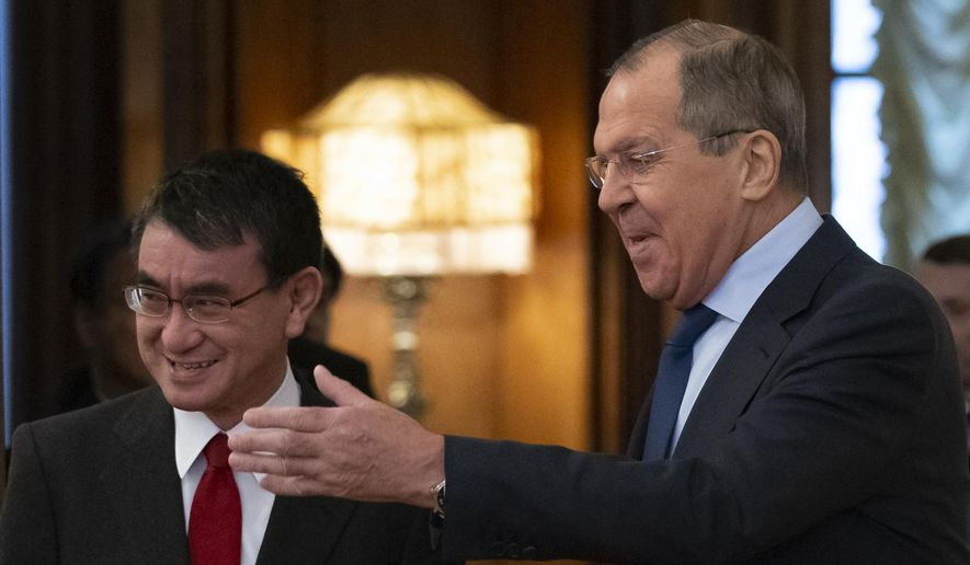 Russian Foreign Minister Sergey Lavrov, right, welcomes Japanese Foreign Minister Taro Kono for the talks in Moscow, Russia, Monday, Jan. 14, 2019. (AP Photo/Alexander Zemlianichenko)