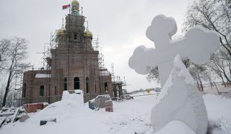 In this photo taken Friday, Jan. 11, 2019, the new church under construction designed in the Russian style in the village Banstol in northwestern Serbia. Topped with Russia-style green and gold onion-shaped domes, the church in this tiny village in northwestern Serbia is still under construction but it has already been dubbed ''Putin's church.'' (AP Photo/Darko Vojinovic)