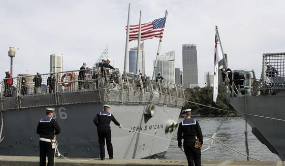 In this Aug. 20, 2008, file photo, Australian sailors tie up the USS John S McCain (DDG-56) as she arrives in Sydney, Australia, for the 100th Anniversary of the Great White Fleet. (AP Photo/Rob Griffith, File)