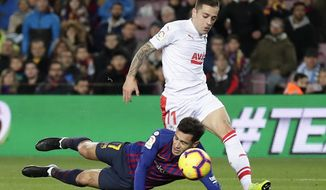 FC Barcelona's Coutinho, left, duels for the ball with Eibar's Ruben Pena during the Spanish La Liga soccer match between FC Barcelona and Eibar at the Camp Nou stadium in Barcelona, Spain, Sunday, Jan. 13, 2019. (AP Photo/Manu Fernandez)