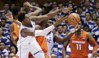 Duke's RJ Barrett and Zion Williamson, rear, reach for a rebound with Syracuse's Oshae Brissett (11) and Frank Howard during the first half of an NCAA college basketball game in Durham, N.C., Monday, Jan. 14, 2019. (AP Photo/Gerry Broome)