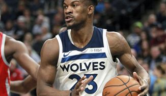 FILE - In this Feb. 13, 2018, file photo, Minnesota Timberwolves guard Jimmy Butler (23) drives against the Houston Rockets during an NBA basketball game, in Minneapolis. The Timberwolves, trying to build off the fresh-start vibe behind 32-year-old interim head coach Ryan Saunders, are ready to show Jimmy Butler what he's been missing. The Wolves play at Philadelphia on Tuesday, Jan. 15, 2019, facing Butler for the first time since he was traded to the 76ers two months ago. (AP Photo/Andy Clayton-King, File)