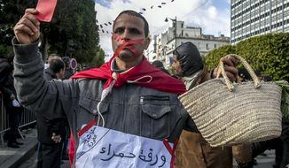 "A gagged Tunisian walks with an empty basket and a red card with a poster reading ""Red card to all politicians without exception"" during a demonstration to mark the eighth anniversary of the democratic uprising in Tunis, Monday, Jan.14, 2019. Tunisia is marking eight years since its democratic uprising amid deepening economic troubles and simmering anger at the revolution's unfulfilled promises. (AP Photo/Hassene Dridi)"