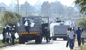 Riot police are seen on a street during a demonstration over the hike in fuel prices in Harare, Zimbabwe, Monday, an. 14, 2019. Zimbabwean President Emmerson Mnangagwa has more than doubled the price of gasoline, hoping the increase will end severe shortages that are fueling public anger even as he departs on a foreign trip to Russia and other countries in search of investment. (AP Photo/Tsvangirayi Mukwazhi)