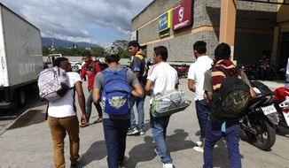 A group of young men arrive at a main bus station to join scores of other migrants forming a caravan to travel to the U.S. border, in San Pedro Sula, Honduras, Monday, Jan. 14, 2019. Yet another caravan of Central American migrants set out late Monday from Honduras, seeking to reach the U.S. border, following the same route followed by thousands on at least three caravans last year. (AP Photo/Delmer Martinez)