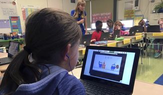 In this Sept. 20, 2018 photo, fifth-grade student Ashlynn De Filippis, left, works math problems on the DreamBox system as teacher Heather Dalton, center rear, works with other students in class at Charles Barnum Elementary School in Groton, Conn. A wide array of apps, websites and software used in schools borrow elements from video games to help teachers connect with students living technology-infused lives. (AP Photo/Michael Melia)