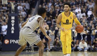 Marquette guard Markus Howard (0) dribbles the ball against Georgetown guard James Akinjo (3) during the first half of an NCAA college basketball game, Tuesday, Jan. 15, 2019, in Washington. (AP Photo/Nick Wass)