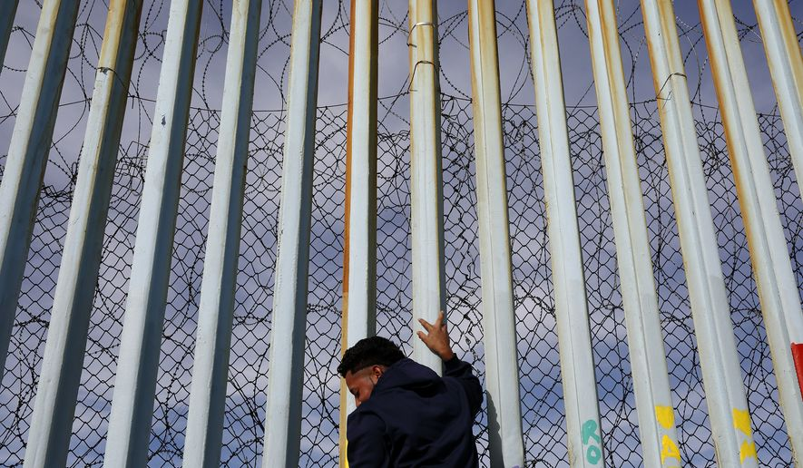 FILE - In this Jan. 8, 2019, file photo, a man holds on to the border wall along the beach, in Tijuana, Mexico. The migrant caravan that was seized upon by U.S. President Donald Trump in the run-up to the 2018 election has quietly dwindled to a few hundred people, with many of them having crossed into the U.S. or put down roots in Mexico. (AP Photo/Gregory Bull, File)