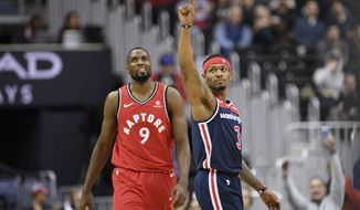 Washington Wizards guard Bradley Beal (3) points in front of Toronto Raptors forward Serge Ibaka (9) during the first half of an NBA basketball game, Sunday, Jan. 13, 2019, in Washington. (AP Photo/Nick Wass)