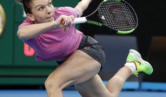Romania's Simona Halep makes a forehand return to Estonia's Kaia Kanepi during their first round match at the Australian Open tennis championships in Melbourne, Australia, Tuesday, Jan. 15, 2019. (AP Photo/Mark Schiefelbein)