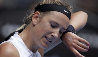 Victoria Azarenka of Belarus wipes sweat from her face during her first round match against Germany's Laura Siegemund at the Australian Open tennis championships in Melbourne, Australia, Tuesday, Jan. 15, 2019. (AP Photo/Aaron Favila)