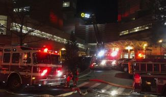 Firefighters work the scene at Hasbro Children's Hospital in Providence, R.I., Tuesday, Jan. 15, 2019. Hospital spokesperson David Levesque says nobody was injured in the Tuesday night fire. He says the fire was contained to the roof and no evacuations had to be made. (AP Photo/Jennifer McDermott)