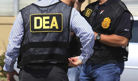 FILE - In this June 13, 2016, file photo, Drug Enforcement Administration (DEA) agents arrive on the scene of a fatal shooting in Florida. U.S. federal narcotics agent, Jose Irizarry, is accused of conspiring with a longtime DEA informant to launder more than $7 million in illicit drug proceeds from the U.S. to traffickers in Colombia, according to several current and former law enforcement officials. (Joe Burbank/Orlando Sentinel via AP, File)