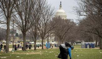 In this Dec. 25, 2018, file photo, the Capitol building is visible as a man picks up garbage during a partial government shutdown on the National Mall in Washington. (AP Photo/Andrew Harnik, File)