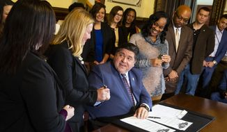 Illinois Gov. J.B. Pritzker offers a pen to state Rep. Anna Moeller, D-Elgin, who with state Sen. Cristina Castro, D-Elgin, left, are sponsors of a bill that prohibits employers from asking about salary history in interviews, during a press conference and signing ceremony Tuesday, Jan. 15, 2019 in the governor's office at the Capitol in Springfield, Ill. Former Gov. Bruce Rauner had vetoed the plan twice, but Pritzker signed an executive order on his first full day in office making the measure applicable to state government hiring. (Rich Saal/The State Journal-Register via AP)