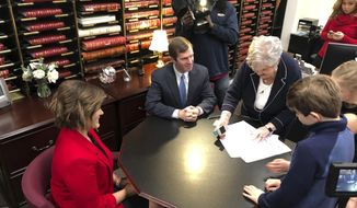 Kentucky Attorney General Andy Beshear, center, watches as Mary Sue Helm, right, reviews his paperwork to run for governor, Tuesday, Jan. 15, 2019, in Frankfort, Ky. Beshear is the second Democrat to file for the seat, joining former state worker Geoff Young. Two other Democrats say they are running for governor: state House Minority Floor Leader Rocky Adkins and former Auditor Adam Edelen. (AP Photo/Adam Beam)