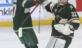 Minnesota Wild goalie Alex Stalock, right, and teammate Marcus Foligno celebrate the Wild's 3-2 shootout win in an NHL hockey game against the Los Angeles Kings on Tuesday, Jan. 15, 2019, in St. Paul, Minn. (AP Photo/Jim Mone)