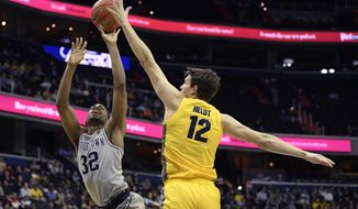 Georgetown guard Kaleb Johnson (32) goes to the basket against Marquette center Matt Heldt (12) during the second half of an NCAA college basketball game, Tuesday, Jan. 15, 2019, in Washington. Marquette won 74-71. (AP Photo/Nick Wass)