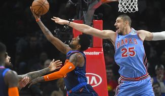Oklahoma City Thunder forward Paul George attempts a reverse layup as Atlanta Hawks center Alex Len (25) defends during the first half of an NBA basketball game, Tuesday, Jan. 15, 2019, in Atlanta. (AP Photo/John Amis)