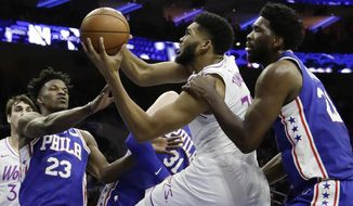 Minnesota Timberwolves' Karl-Anthony Towns, center, tries to get a shot past Philadelphia 76ers' Joel Embiid, right, and Jimmy Butler during the first half of an NBA basketball game, Tuesday, Jan. 15, 2019, in Philadelphia. (AP Photo/Matt Slocum)