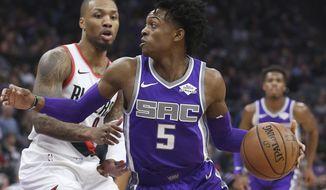 Sacramento Kings guard De'Aaron Fox, right, drives against Portland Trail Blazers guard Damian Lillard, left, during the first quarter of an NBA basketball game Monday, Jan. 14, 2019, in Sacramento, Calif. (AP Photo/Rich Pedroncelli)
