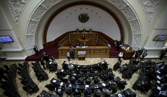Lawmakers attend a session at the opposition-controlled National Assembly to debate actions against Venezuelan President Nicolas Maduro in Caracas, Venezuela, Tuesday, Jan. 15, 2019. The president is under heightened pressure from opposition politicians and foreign leaders urging him to step down. (AP Photo/Fernando Llano)