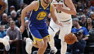 Golden State Warriors guard Klay Thompson, front, tracks down a loose ball as Denver Nuggets center Nikola Jokic follows in the first half of an NBA basketball game, Tuesday, Jan. 15, 2019, in Denver. (AP Photo/David Zalubowski)