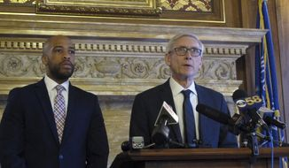 Wisconsin Democratic Gov. Tony Evers, right, says he told told Republican lawmakers during a private meeting that he will push for Medicaid expansion, but won't propose eliminating the state's economic development agency, on Tuesday, Jan. 15, 2019, in Madison, Wis. Standing at left is Lt. Gov. Mandela Barnes. (AP Photo/Scott Bauer)