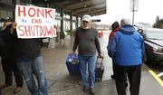 A man heading into the Sacramento International Airport passes demonstrators calling for President Donald Trump and Washington lawmakers to end the shutdown, Wednesday, Jan. 16, 2019, in Sacramento, Calif. More than two dozen federal employees and supporters called for an end to the partial government shutdown now in its fourth week. (AP Photo/Rich Pedroncelli)
