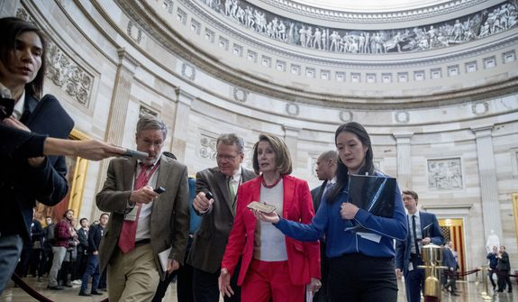 House Speaker Nancy Pelosi of Calif., center, speaks to reporters as she leaves an event with furloughed federal workers amid the partial government shutdown, Wednesday, Jan. 16, 2019, on Capitol Hill in Washington. (AP Photo/Andrew Harnik)