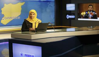 This undated photo provided by Iranian state television's English-language service, Press TV, shows American-born news anchor Marzieh Hashemi at studio in Tehran, Iran.  The elder son of Hashemi says his mother is being held in the United States, but has not been charged with anything.  Hussein Hashemi says she was detained Sunday,  Jan. 13, 2019, as she was leaving St. Louis for Denver. He says she had filmed a Black Lives Matter documentary in St. Louis after visiting family in New Orleans.  (Press TV via AP)