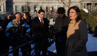White House press secretary Sarah Huckabee Sanders talks with reporters outside the White House, Wednesday, Jan. 16, 2019, in Washington. (AP Photo/ Evan Vucci)