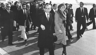 FILE - In this Jan. 16, 1979 file photo, Shah Mohammad Reza Pahlavi and Empress Farah walk on the tarmac at Mehrabad Airport in Tehran, Iran, to board a plane to leave the country. Wednesday, Jan. 16, 2019 marks the 40th anniversary of the shah abandoning his Peacock Throne and leaving his nation for the last time in his life, setting the stage for the country's 1979 Islamic Revolution only a month later. (AP Photo, File)