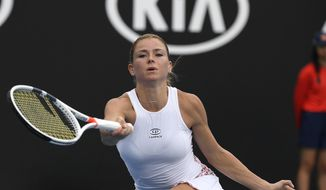 Italy's Camila Giorgi makes a forehand return to Poland's Iga Swiatek during their second round match at the Australian Open tennis championships in Melbourne, Australia, Thursday, Jan. 17, 2019. (AP Photo/Andy Brownbill)