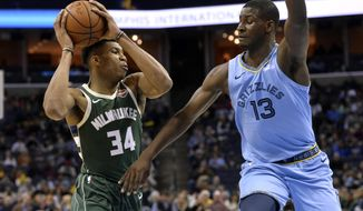 Milwaukee Bucks forward Giannis Antetokounmpo (34) controls the ball against Memphis Grizzlies forward Jaren Jackson Jr. (13) in the first half of an NBA basketball game Wednesday, Jan. 16, 2019, in Memphis, Tenn. (AP Photo/Brandon Dill)