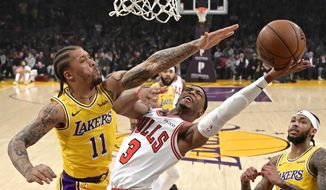 Chicago Bulls guard Shaquille Harrison, center, shoots as Los Angeles Lakers forward Michael Beasley, left, defends along with forward Brandon Ingram during the first half of an NBA basketball game Tuesday, Jan. 15, 2019, in Los Angeles. (AP Photo/Mark J. Terrill)
