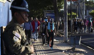 Police stand by as locals begin their journey north toward the U.S. border, during a migrant caravan passing through the capital of San Salvador, El Salvador, early Wednesday, Jan. 16, 2019. Migrants fleeing Central America's Northern Triangle region comprising Honduras, El Salvador and Guatemala routinely cite poverty and rampant gang violence as their motivation for leaving. (AP Photo/Salvador Melendez) **FILE**
