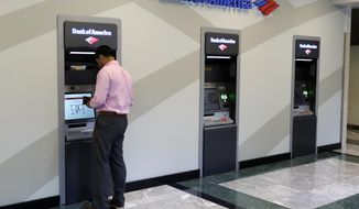 FILE- In this July 9, 2018, file photo a customer makes a transaction at a Bank of America ATM at the company's headquarters in Charlotte, N.C. Bank of America Corp.  reports financial results Wednesday, Jan. 16, 2019. (AP Photo/Chuck Burton, File)