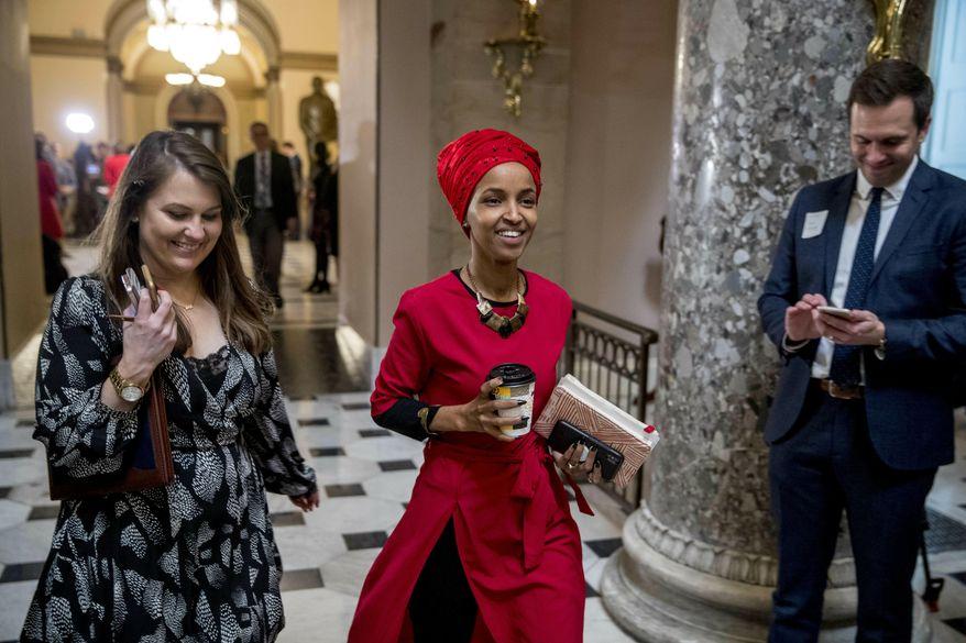 Rep. Ilhan Omar, D-Minn., center, walks through the halls of the Capitol Building in Washington, Wednesday, Jan. 16, 2019. (AP Photo/Andrew Harnik)