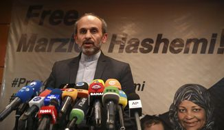 Paiman Jebeli, deputy chief of Iran's state IRIB broadcaster gives a press briefing about American-born news anchor on Iranian state television's English-language service, Marzieh Hashemi, shown in banner, in Tehran, Iran, Wednesday, Jan. 16, 2019. Hashemi has been arrested after flying into the U.S., the broadcaster reported Wednesday. The reported detention of Press TV's Hashemi, born Melanie Franklin of New Orleans, comes as Iran faces increasing criticism of its own arrests of dual nationals and others with Western ties, previously used as bargaining chips in negotiations with world powers. (AP Photo/Vahid Salemi)