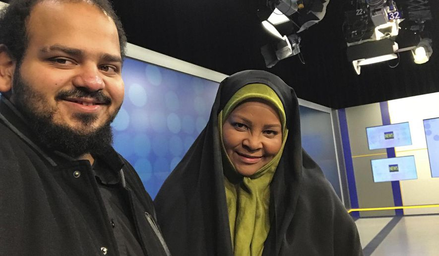 In this undated photo provided by Iranian state television's English-language service, Press TV, American-born news anchor Marzieh Hashemi, right, smiles as she stands with her son in Tehran, Iran. The elder son of Hashemi says his mother is being held in the United States, but has not been charged with anything.  Hussein Hashemi says she was detained Sunday,  Jan. 13, 2019, as she was leaving St. Louis for Denver. He says she had filmed a Black Lives Matter documentary in St. Louis after visiting family in New Orleans.  (Press TV via AP)