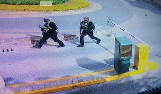 "In this grab taken from security camera footage released to the local media, heavily armed attackers walk in the compound of a hotel, in Nairobi, Kenya, Tuesday, Jan. 15, 2019. Extremists launched an attack on a luxury hotel in Kenya's capital, sending people fleeing in panic as explosions and heavy gunfire reverberate through the neighborhood. A police officer says he saw bodies, ""but there was no time to count the dead."" Al-Shabab _ the Somalia-based extremist group _ is claiming responsibility. (Security Camera Footage via AP)"