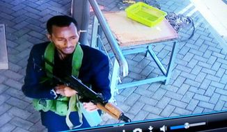 "In this grab taken from security camera footage released to the local media, an armed attacker walks in the compound of a hotel, in Nairobi, Kenya, Tuesday, Jan. 15, 2019. Extremists launched an attack on a luxury hotel in Kenya's capital, sending people fleeing in panic as explosions and heavy gunfire reverberate through the neighborhood. A police officer says he saw bodies, ""but there was no time to count the dead."" Al-Shabab _ the Somalia-based extremist group _ is claiming responsibility. (Security Camera Footage via AP)"