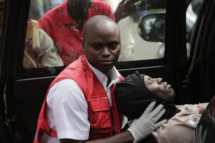 A wounded member of Kenyan special forces is carried from a US embassy diplomatic vehicle into an ambulance by red cross paramedics at the scene Wednesday, Jan. 16, 2019 in Nairobi, Kenya. Extremists stormed a luxury hotel in Kenya's capital on Tuesday, setting off thunderous explosions and gunning down people at cafe tables in an attack claimed by Africa's deadliest Islamic militant group (AP Photo/Khalil Senosi)