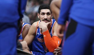 FILE - In this Jan. 1, 2019, file photo, New York Knicks center Enes Kanter jokes with teammates during a timeout the first half of the team's NBA basketball game against the Denver Nuggets, in Denver. Turkish prosecutors are seeking an international arrest warrant for Knicks player Enes Kanter, accusing him of membership in a terror organization. (AP Photo/David Zalubowski, File)