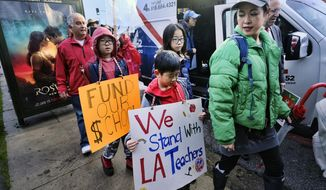 Parents, teachers and students carry signs and picket in front of Hamilton High School, Wednesday, Jan. 16, 2019, in Los Angeles during a citywide teacher strike. (AP Photo/Richard Vogel)