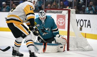 San Jose Sharks goaltender Martin Jones (31) defends on a shot from Pittsburgh Penguins left wing Tanner Pearson (14) during the second period of an NHL hockey game in San Jose, Calif., Tuesday, Jan. 15, 2019. (AP Photo/Tony Avelar)