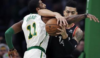 Boston Celtics guard Kyrie Irving (11) and Toronto Raptors guard Danny Green, right, tangle as they compete for the ball during the first quarter of an NBA basketball game in Boston, Wednesday, Jan. 16, 2019. (AP Photo/Charles Krupa)