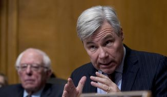 Sen. Sheldon Whitehouse, D-R.I., right, accompanied by Sen. Bernie Sanders, I-Vt., left, questions Andrew Wheeler as he testifies at a Senate Environment and Public Works Committee hearing to be the administrator of the Environmental Protection Agency, on Capitol Hill in Washington, Wednesday, Jan. 16, 2019. (AP Photo/Andrew Harnik) ** FILE **